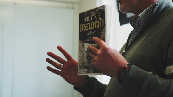 A man holding a book about Irish history.