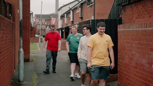 A group of four boys walking down an alleyway.